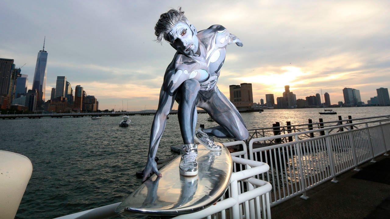 Der Silver Surfer als Cosplay durch den Verkehr von New York surfend