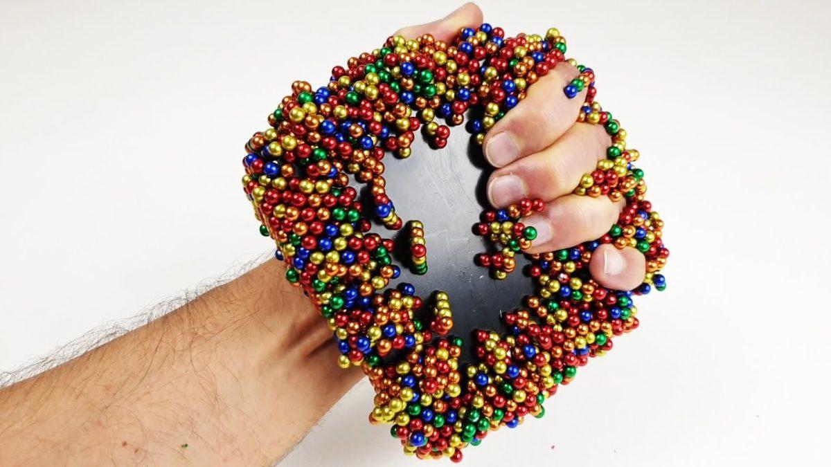 Viele kleine magnetische Kugeln gegen einen großen Monster Magnet in Zeitlupe